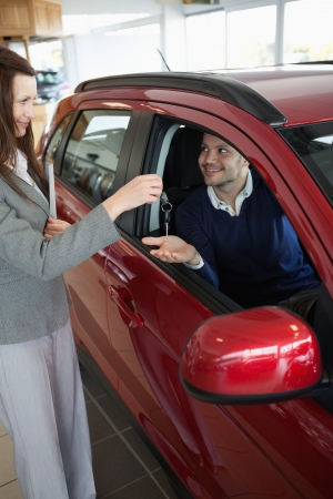 renter: Businesswoman giving car keys to a customer in a garage