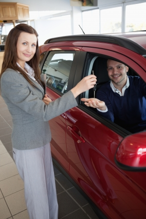 Man tending his hand while receiving car keys in adealership Stock Photo - 16208919