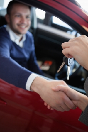 Customer receiving car keys while shaking hand in a garage Stock Photo - 16208839