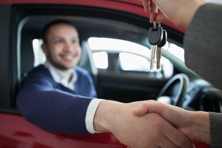 Woman giving car keys while shaking hand in a dealership Stock Photo - 16208872