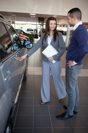 renter: Woman holding car handle in a dealership Stock Photo