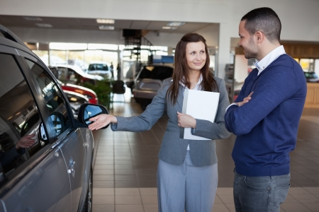 Businesswoman presenting a car to a client in a dealership photo