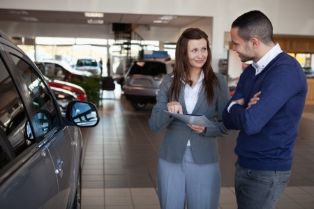 Woman explaining something to a man in a dealership photo