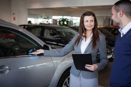 Woman presenting something to a man in a dealership photo