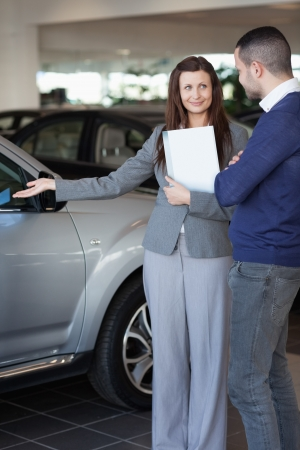 Woman showing a car to a client in a dealership photo