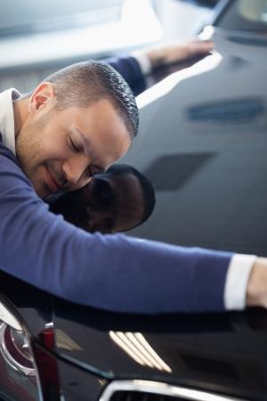 cherishing: Man embracing a car in a garage