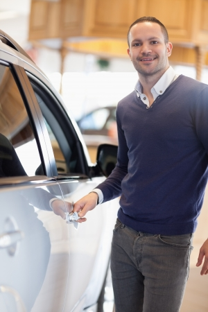 Man holding a car handle while smiling in a garage photo