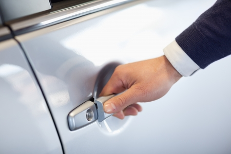 Close up of a man opening a car door in a garage Stock Photo - 16204028