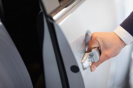 manejar: El hombre abre la puerta del coche en un garaje Foto de archivo