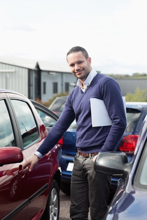 renter: Man holding a car handle while holding a file outdoors Stock Photo