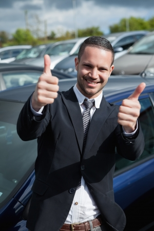 Businessman raising his thumbs while smiling outdoors Stock Photo - 16207722