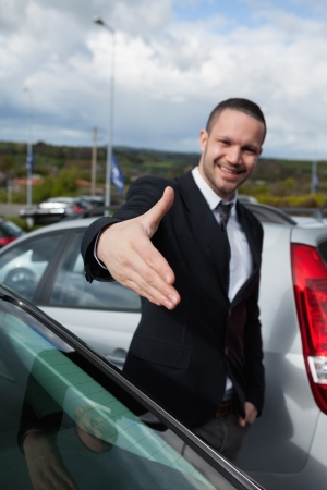 Businessman wanting to shake the hand of someone outdoors Stock Photo - 16207425