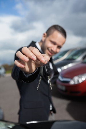 Happy businessman holding car keys outdoors photo