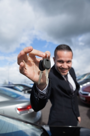 happy dealer holding car keys by his fingertips outddors Stock Photo - 16204751