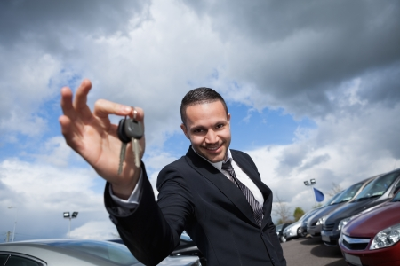 well dressed  holding: Happy seller holding car keys outdoors Stock Photo