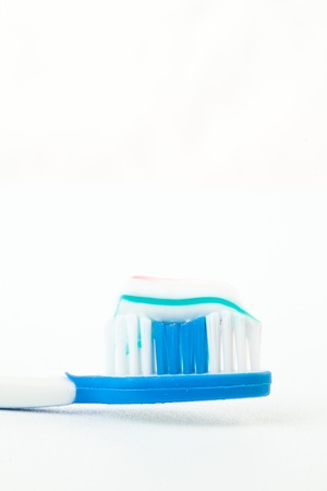 rotten teeth: Toothpaste on a toothbrush against white background