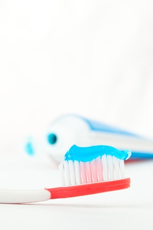 rotten teeth: Red toothbrush next to a tube of toothpaste against white background Stock Photo
