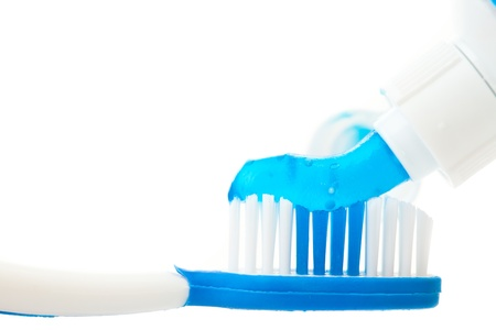 rotten teeth: Close up of a toothpaste on a toothbrush against white background