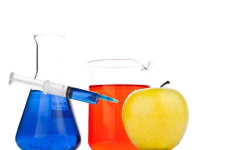 modifying: Syringe pricking an apple against a white abckground Stock Photo