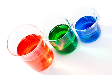 Three beakers of different colour and size against a white background Stock Photo - 16201012