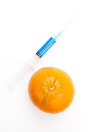 Orange next to a syringe against a white background Stock Photo - 16199175