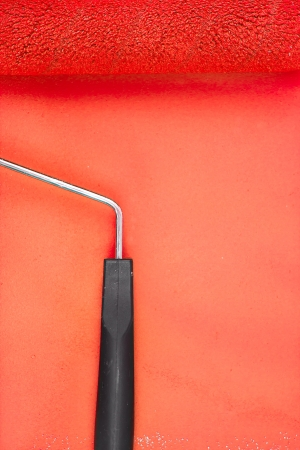red paint roller: Red paint roller with handle on a background