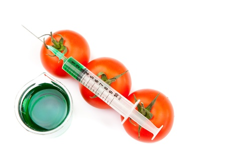 modifying: Beaker next to syringe on tomatoes against a white background