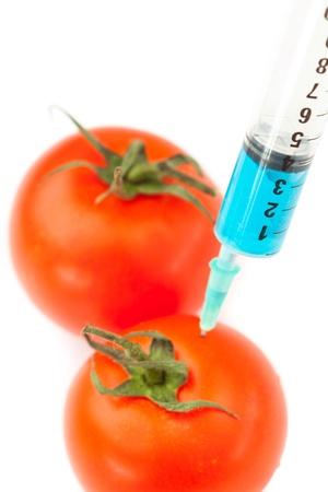modifying: Syringe pricking a tomato against a white background