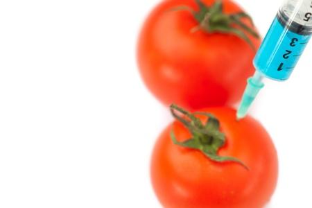 modifying: Syringe pricking tomato against a white background Stock Photo