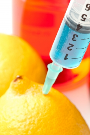 Close up of syringe into a lemon against a white background Stock Photo - 16203090