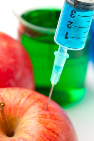 Close up of a syringe injecting liquid into an apple against a white background Stock Photo - 16207878