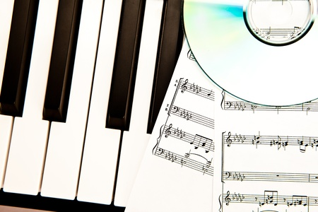 scores: Compact disc and music scores placed on piano keyboard Stock Photo