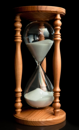 Sand flowing inside of hourglass against a black background photo