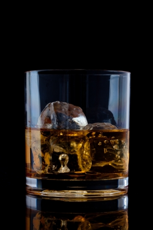 Glass with whiskey against a black background Stock Photo - 16201911