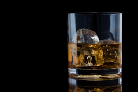 Tumbler glass with whiskey against a black background Stock Photo - 16201822