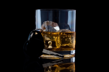 Tumbler glass with whiskey and a car key against a black background