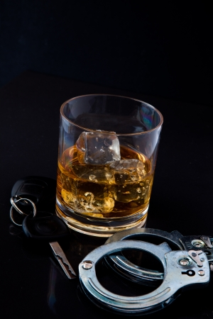 Whiskey on the rocks with car key and handcuff against a black background Stock Photo - 18683340