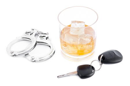Handcuff a whiskey and a car key against a white background Stock Photo