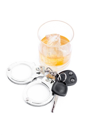 inebriated: Car key next to a whiskey and a handcuff against a white background