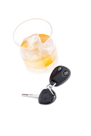 Car key and a whiskey on the rocks against a white background