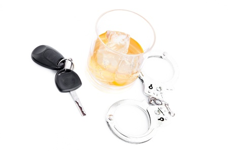 inebriated: Tumbler glass with whiskey with car key and handcuff against a white background Stock Photo