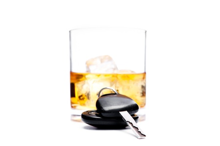 Car key in front of a glass of whiskey against a white background