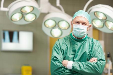 cirujano: Cirujano sonriente con los brazos cruzados mientras est� de pie en una sala quir�rgica