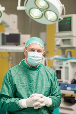 Surgeon smiling while crossing his hands in a surgical room photo