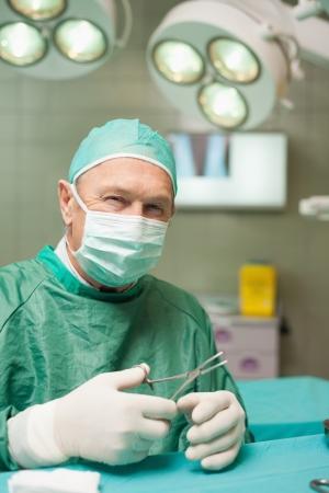cirujano: M�dico sonriente sosteniendo unas tijeras en una sala quir�rgica