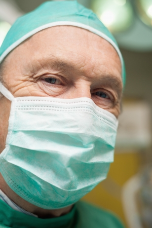 operation gown: Close up of a surgeon with a face mask on in a surgical room