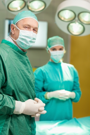 Two surgeon crossing their hands while standing in a surgical room photo