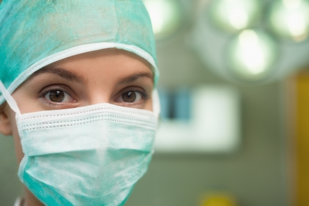 operation gown: Close up of a woman wearing surgical gear in a surgical room