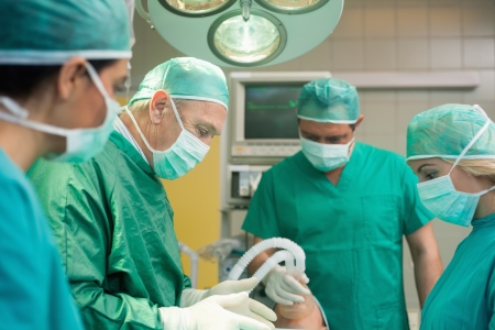 Surgery team operating in a surgical room photo