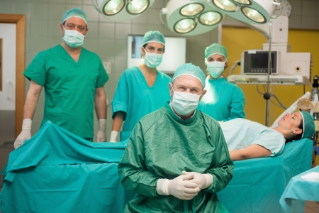 operation gown: Surgical team around a patient in a surgical room Stock Photo